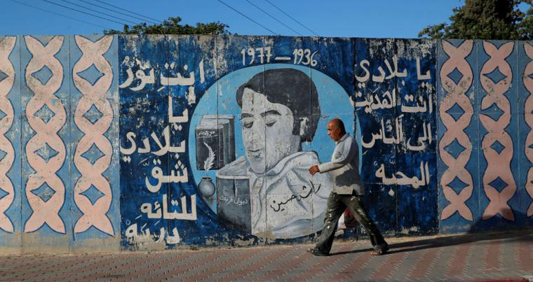 "A man walks past a mural with writing in Arabic that reads: ""My country, you gave us love and light which revealed paths for the lost"" in the Israeli Arab city of Umm al-Fahm. (Reuters)"