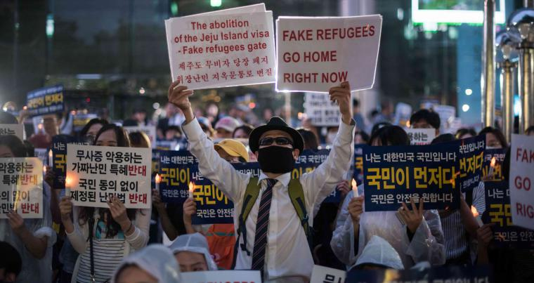 Anti-immigration activists attend a protest against a group of asylum-seekers from Yemen, in Seoul on June 30, 2018. (AFP)