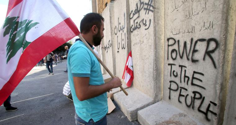 Don't you wish! A Lebanese young man, carrying the national flag, reads a graffiti on concrete blast walls on the road leading to the governmental palace in Beirut. (AFP)