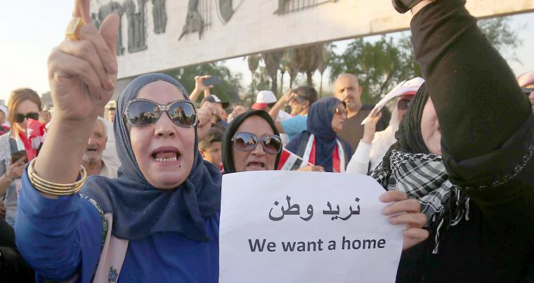 An Iraqi woman holds a sign and chants slogans during a demonstration against unemployment in Baghdad's Tahrir Square. (AFP)