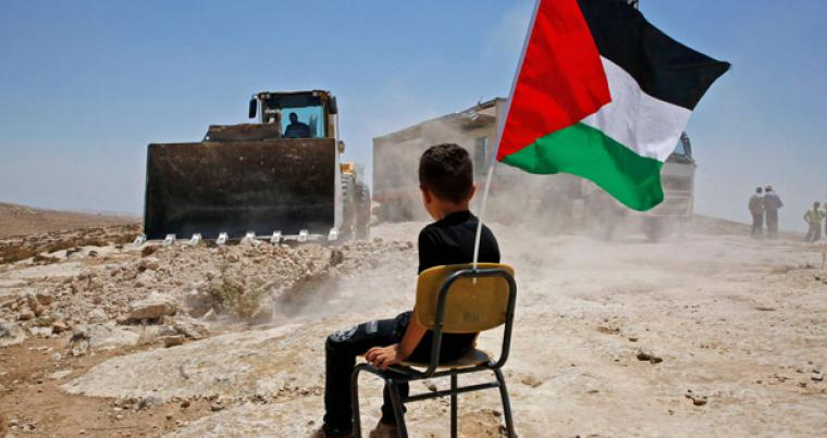 At all costs. A Palestinian boy sits on a chair with a national flag as Israeli authorities demolish a school site in the village of Yatta, on July 11.         (AFP)