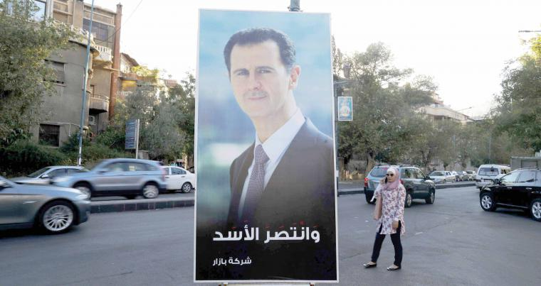 "A Syrian woman talks on a mobile phone next to a poster of President Bashar Assad with Arabic that reads, ""Assad has Triumphed,"" in Damascus. (AP)"