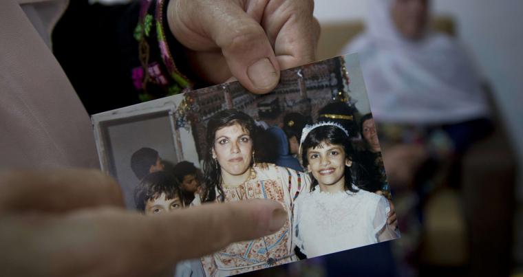 Fadwa Tlaib, an aunt of Rashida Tlaib points to a young Rashida in a 1987 picture with her mother Fatima and brother Nader at the family house in the West Bank village of Beit Ur al-Foqa. (AP)