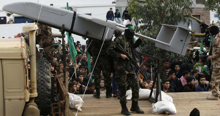 Palestinian members of al-Qassam Brigades, the armed wing of the Hamas movement, display a home-made drone during a military parade marking the 27th anniversary of Hamas' founding, in Gaza City December 14, 2014. (Reuters)