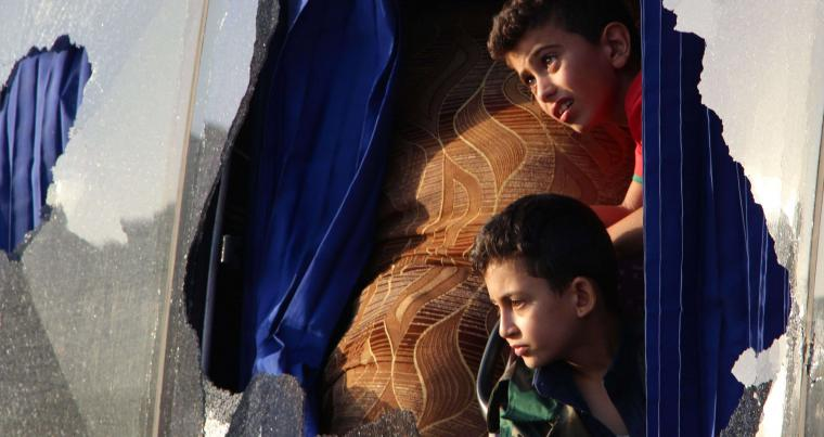 Evacuated Syrian boys from Fuaa and Kafraya towns in the Idlib province, look out of a broken bus window during evacuating pro-regime fighters and inhabitants. (AFP)
