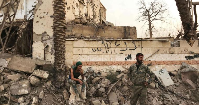 Syrian government forces stand next to a damaged building in a northeastern district of Deir Ezzor, last November. (AFP)