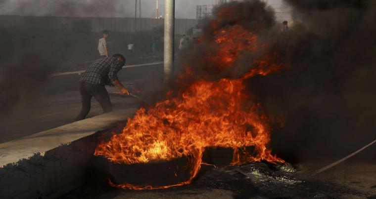 Protesters burn tires during a protest at the entrance of Erez border crossing between Gaza and Israel, in the northern Gaza Strip, Tuesday, Sept. 18, 2018. (AP)