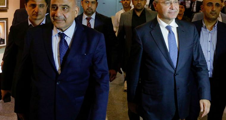 Iraq's new President Barham Salih (centre right) walks with new Prime Minister Adel Abdul Mahdi (centre left) in the parliament building in Baghdad, on October 2. (AP)