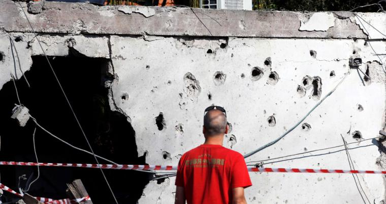 A man looks at a building damaged by a rocket fired from the Gaza Strip overnight, in the Israeli city of Ashkelon, on November 13. (Reuters)