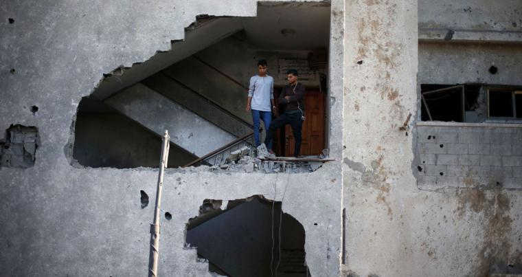 Palestinians look out of their house that was damaged in an Israeli air strike, in Gaza City, on November 13. (Reuters)