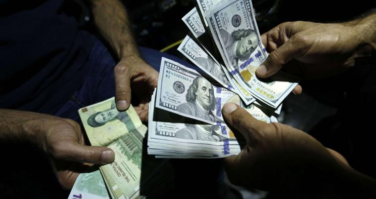 A man exchanges Iranian Rials against US Dollars at an exchange shop in Tehran, on October 2. (AFP)
