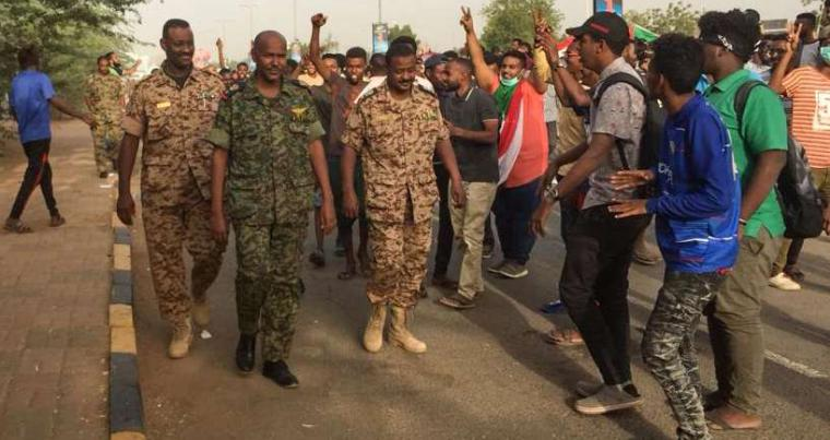Sudanese protesters cheer for passing soldiers near the military headquarters in the capital Khartoum on April 11. (AFP)