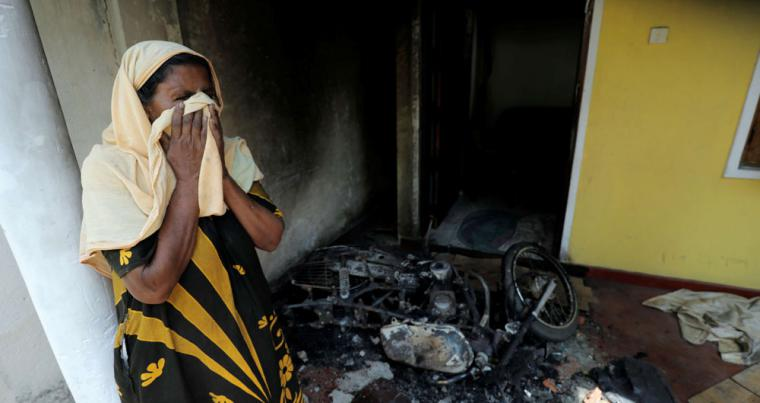 A Muslim woman reacts next to a burnt motor bike and her house after a mob attack in Kottampitiya, Sri Lanka, May 14. (Reuters)