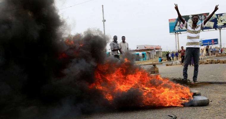 A Sudanese protester gestures near burning tyres used to erect a barricade on a street, demanding that the country's Transitional Military Council handover power to civilians, in Khartoum, Sudan June 4, 2019. (Reuters)