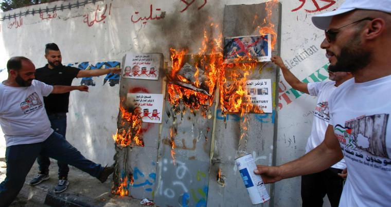 Palestinian men burn protest signs showing the crossed-out faces of (L to R) Israeli Prime Minister Benjamin Netanyahu, US President Donald Trump and King Hamad al-Khalifa of Bahrain in the occupied West Bank, on June 16, 2019/ (AFP)