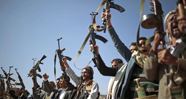 Tribesmen loyal to Houthi rebels hold up their weapons as they attend a gathering to show their support for the ongoing peace talks in Sanaa, Yemen, December 13, 2018. (AP)