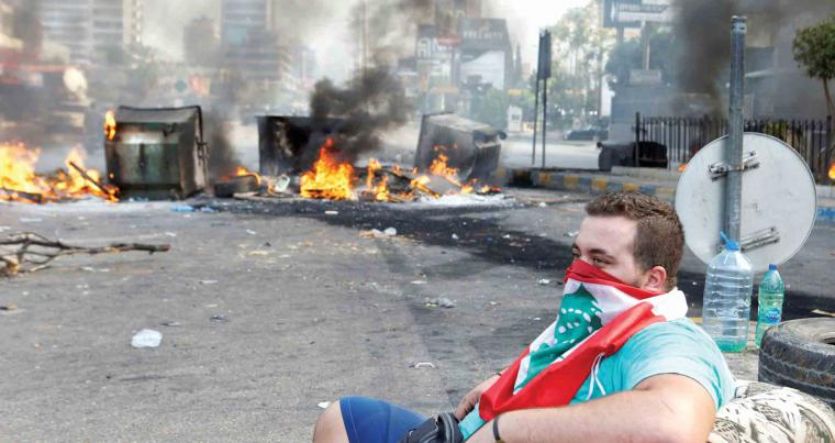 A blend of defiance and hope. A demonstrator sits on a sofa with a Lebanese flag covering his face near burning tyres during a protest over deteriorating economic conditions in Jdeideh, Lebanon, October 18. (Reuters)