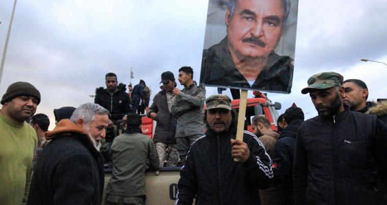 People raise a picture of Libyan strongman Khalifa Haftar in the eastern Libyan city of Benghazi, January 3. (AFP)