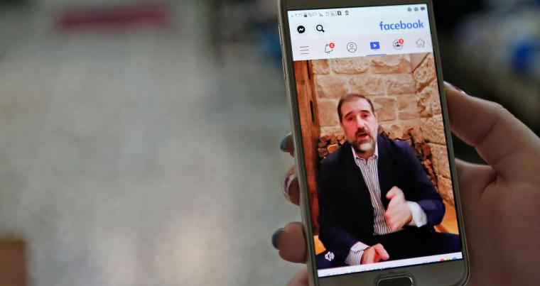 A woman watches the Facebook video of Syrian businessman Rami Makhlouf on her mobile in Syria's capital Damascus. (AFP)