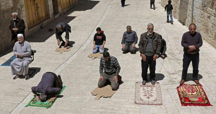 Palestinians perform Friday prayers on the street outside of the closed-down Al-Qazazin mosque in the old town of the West Bank city of Hebron. (AFP)