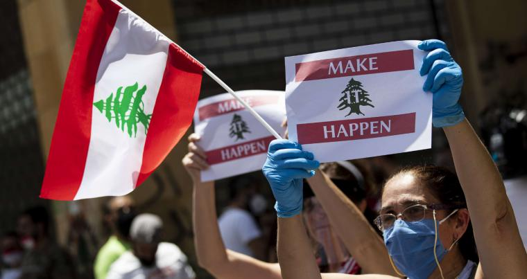 Anti-government protesters shout slogans during ongoing protests in front of the Ministry of Economy, in downtown Beirut on May 18. (AFP)