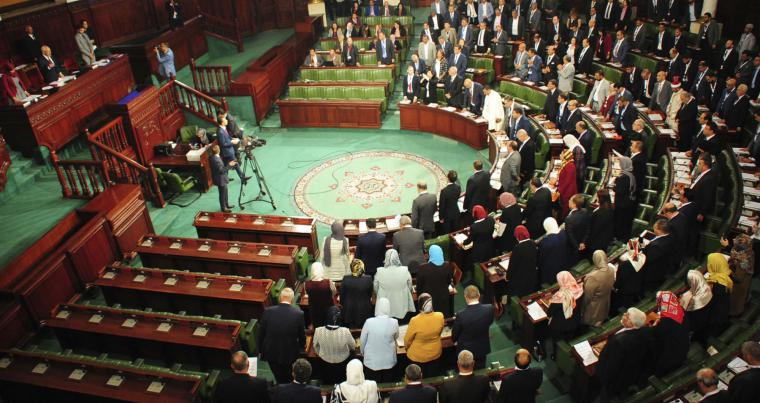 Tunisian National Assembly members stand during a parliamentary session. (AP)
