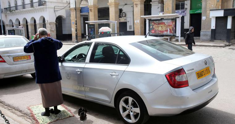 A man prays outside a mosque near his car in Algiers. (AFP)
