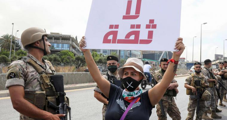 "A Lebanese anti-government protester holds a placard reading ""No Trust"" in front of army soldiers as she takes part in a demonstration near the presidential palace in Baabda, east of Beirut, on June 25, 2020. (AFP)"