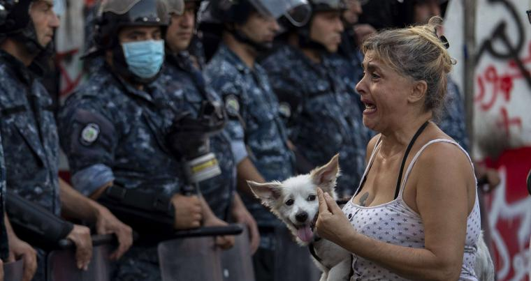 An anti-government protester cries as she holds her dog during ongoing protests in Beirut, Lebanon. (AP)
