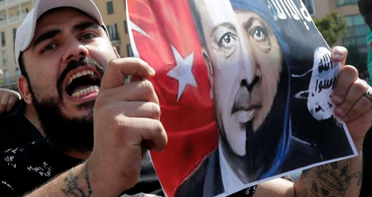 A Kurdish protester holds a placard bearing the portrait of Turkish President Recep Tayyip Erdogan during a demonstration against the latest Turkish military offensive in northeastern Syria, in central Beirut's Martyrs Square on October 13, 2019. (AFP)