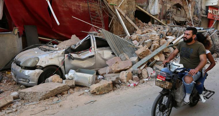 A man rides on a motorbike near rubble from damaged buildings after Beirut blast, August 6, (Reuters)