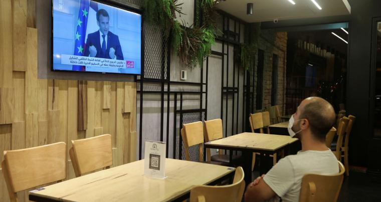 An employee watches a news conference of French President Emmanuel Macron on the political situation in Lebanon, inside an empty restaurant in Beirut, Lebanon, September 27.(REUTERS)