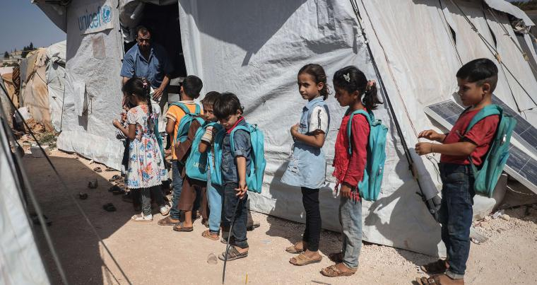 Children stand in front of a tent classroom at a school in the town of Batenta camp in Idlib governorate, Syria, September 27. (DPA)