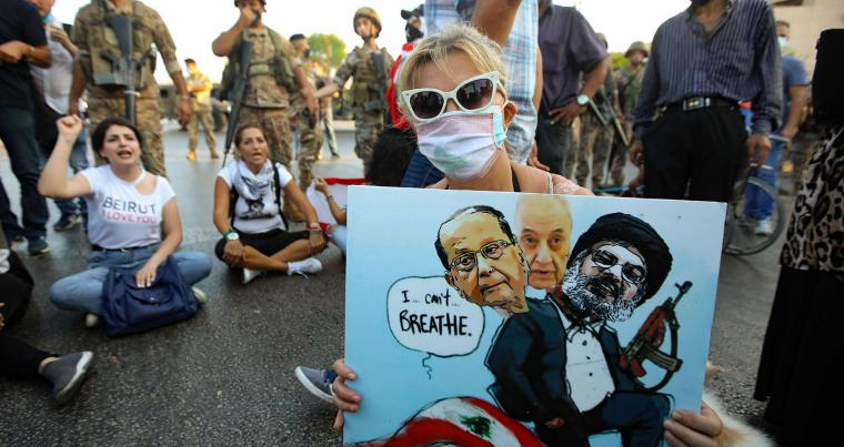 A Lebanese anti government protester holds a placard, in Beirut,  with a cartoon of (L-R) President Michel Aoun, Parliament Speaker Nabih Berri and head of the Shia Hezbollah movement Hassan Nasrallah, September 12. (AFP)