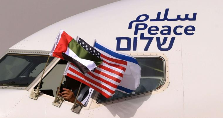 "The Emirati, Israeli and US flags attached to an air-plane of Israel's El Al, adorned with the word ""peace"" in Arabic, English and Hebrew, upon its arrival at the Abu Dhabi airport in the first-ever commercial flight from Israel to the UAE, on August 31."