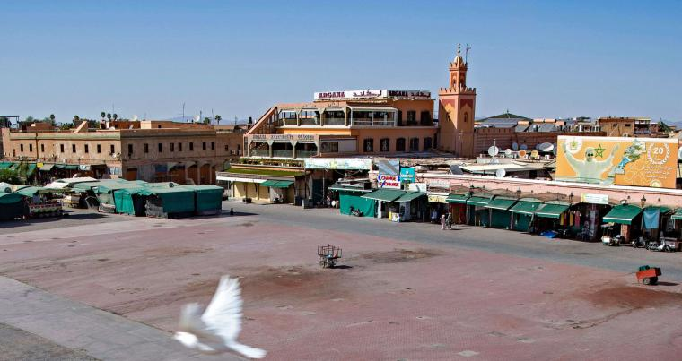 A few people walk by mostly-closed stalls at the Jemaa el-Fna square in the Moroccan city of Marrakesh. (AFP)