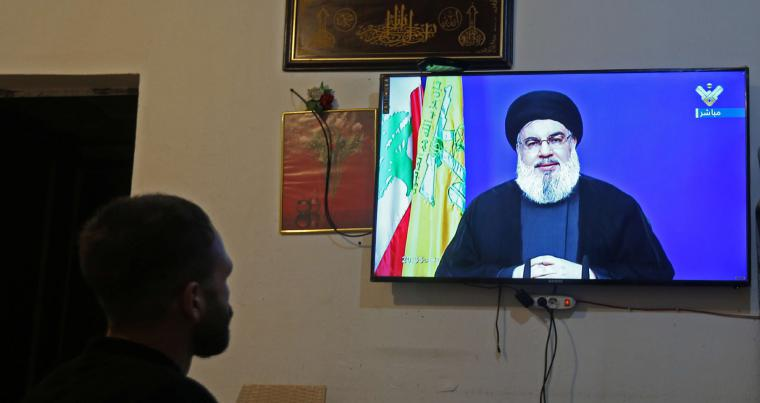 A man watches Lebanon's Hezbollah leader Sayyed Hassan Nasrallah speaking on television, inside a shop in Houla, southern Lebanon September 29. (REUTERS)
