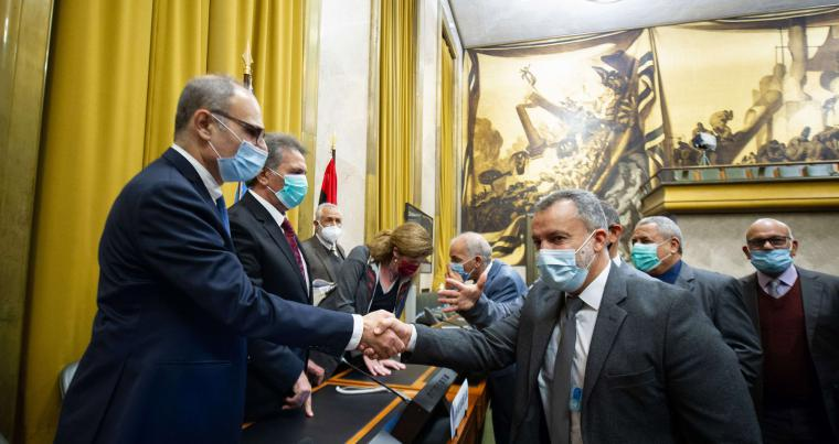Representative of Libya's two rival factions shaking hands after a signing ceremony, on October 23, in Geneva. (AFP)
