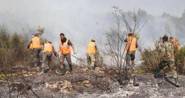 Firefighters work to put out a forest fire in Safita, Syria. (Reuters)