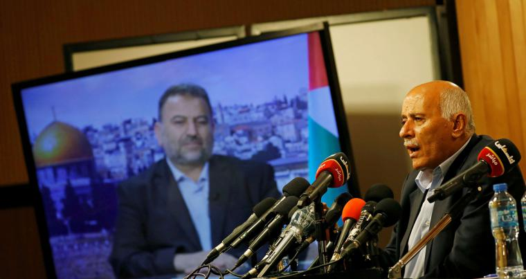 Senior Fatah official Jibril Rajoub speaks as deputy Hamas chief Saleh Arouri appears on a television screen during a video conference, in Ramallah, last July. (REUTERS)