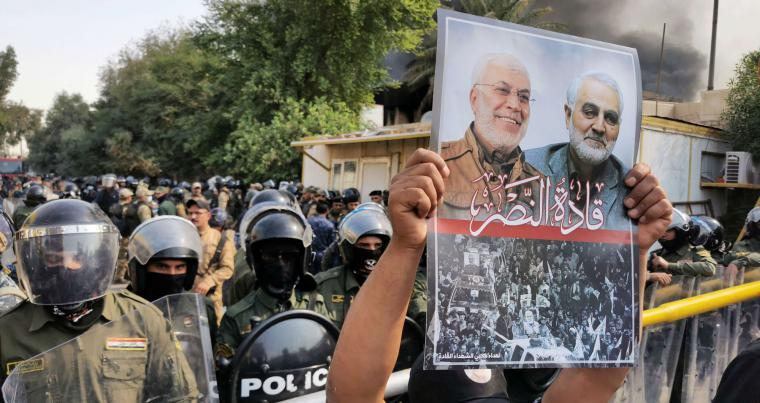 A demonstrator holds a picture of Iran's Quds Force commander Qassem Soleimani and Iraqi militia leader Abu Mahdi al-Muhandis, who were killed last year. (REUTERS)