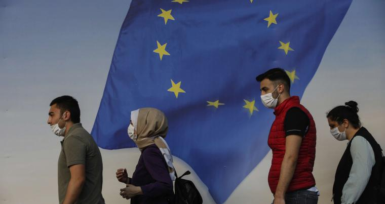 Backdropped by a poster with a European Union flag, people, wearing masks to help protect against the spread of coronavirus walk in Istanbul, Friday, Oct. 2, 2020. (AP)