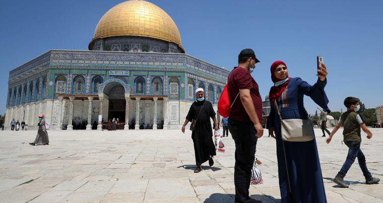 A Palestinian woman takes a selfie in front of the Dome of the Rock before Friday prayers in Jerusalem's Old City. (REUTERS)