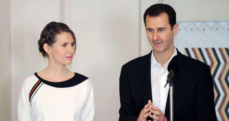 A file picture shows Syrian President Bashar Assad (R) speaking next to his wife Asma as they receive members of the army in the capital Damascus. (SANA)