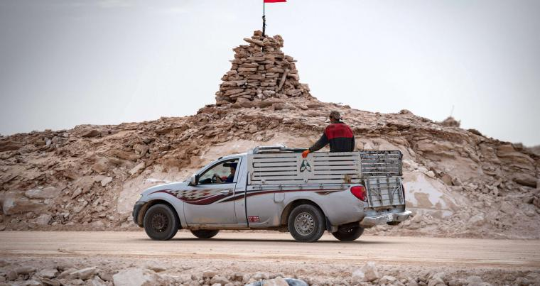 A pickup truck passes by a hilltop manned by Moroccan soldiers on a road between Morocco and Mauritania in Guerguerat located in the Western Sahara, on November 23, 2020.( AFP)