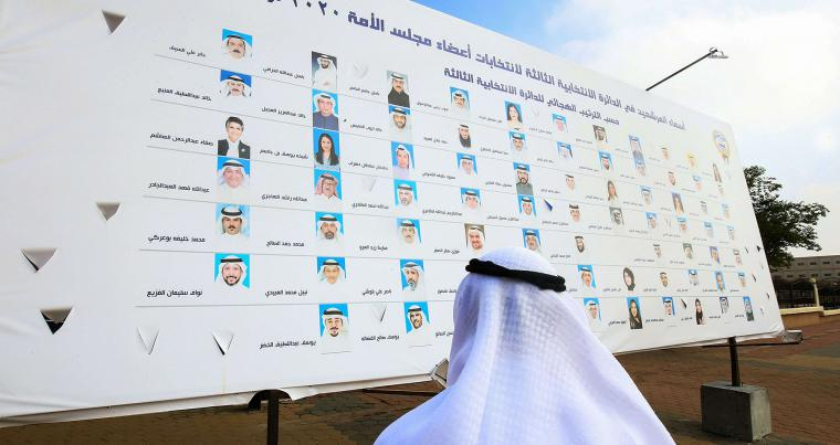 A Kuwaiti man looks at a billboard featuring the candidates running for parliamentary elections in Kuwait City, on November 30, 2020. (AFP)