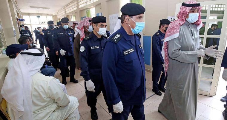Kuwaiti Prime Minister Sheikh Sabah Al-Khaled Al-Hamad Al-Sabah (R) arrives to cast his votes at a polling station in Kuwait City during parliamentary elections, December 5. (AFP)