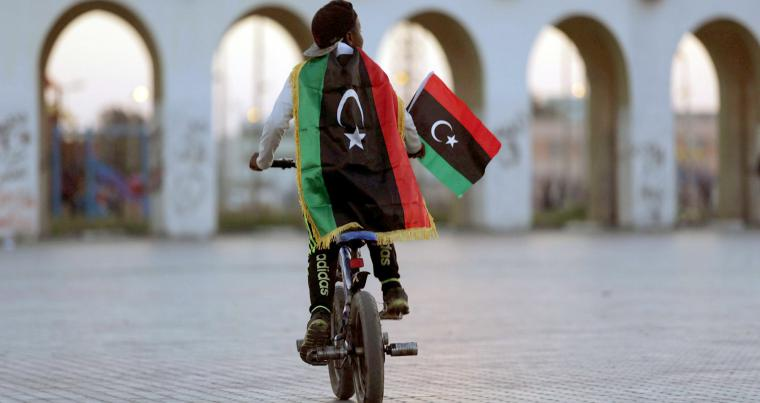 A boy wearing a Libyan flag rides a bike in Benghazi, Libya. (REUTERS)