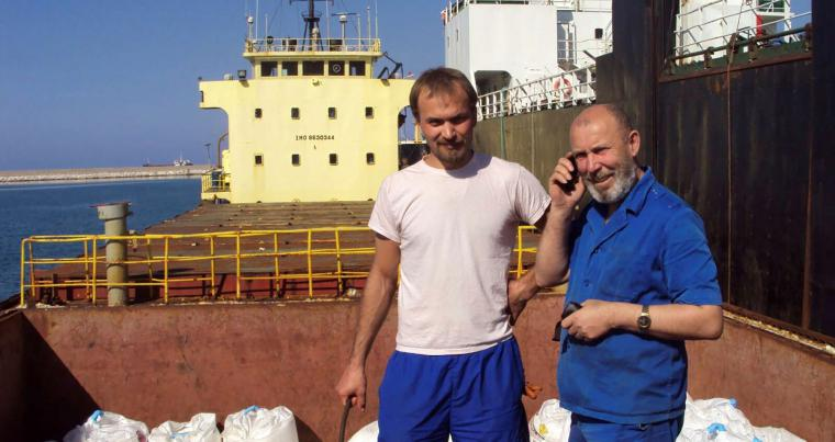 Boris Prokoshev (R), captain of cargo vessel Rhosus, and boatswain Boris Musinchak pose next to a freight hold loaded with ammonium nitrate in the port of Beirut, Lebanon, in 2014. (REUTERS)