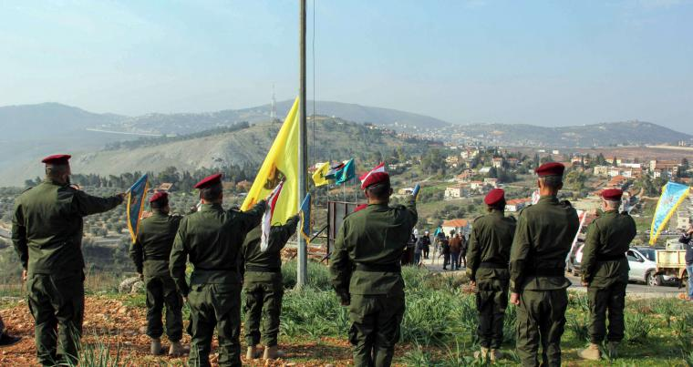 Lebanon's Hezbollah members raise a flag bearing portraits of (L-R) slain Iraqi commander Abu Mahdi al-Muhandis, Hezbollah's Imad Moghniyeh, and IRGC's Qasem Soleimani, on a hill facing the Israeli town of Metula on the border with Lebanon, on January 3, (AFP)
